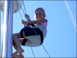 My daughter (Carolyne age 9 at the time) up the mast in the bosuns chair to replace a light.