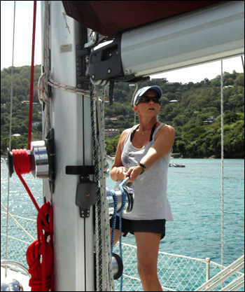 Preparing for a sail-away departure, Heather raises the main sail prior to hoisting the anchor in a cozy harbor in Bequia, Grenadines