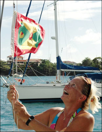Heather raises the courtesy flag for the island nation of Grenada, s/v WILD HAIR's current home