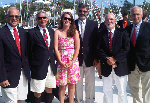 Lisa in her bright pink dress surrounded by her crewmates in their Bermuda shorts and high socks